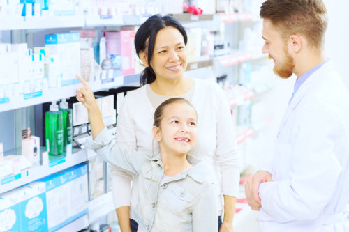 male pharmacist and a woman customer with her daughter